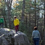 Children enjoying a glacial erratic on a hike.