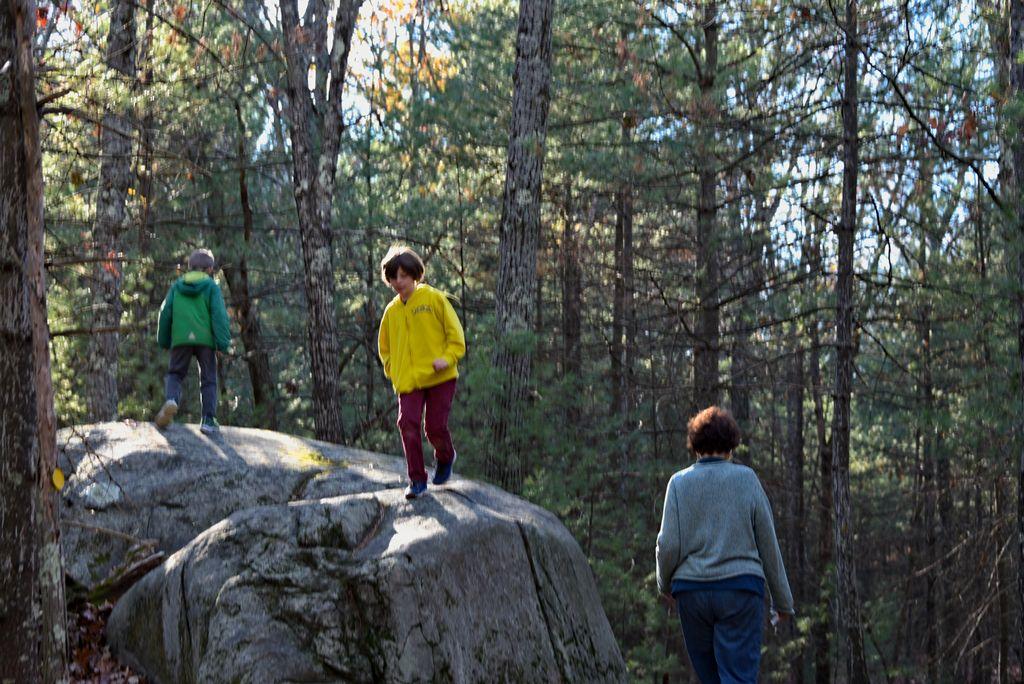 Children enjoying a glacial erratic on a hike.